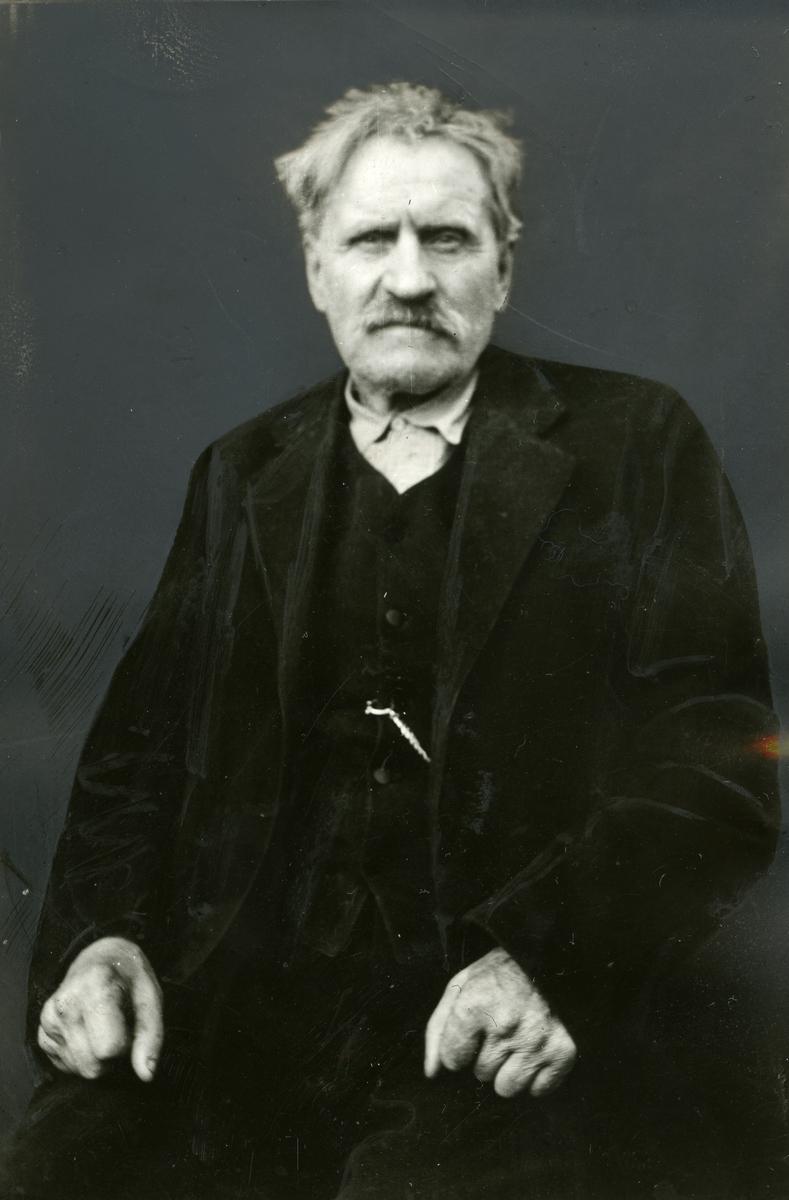 Portrett av en eldre mann. Mannen er iført en mørk dress.
