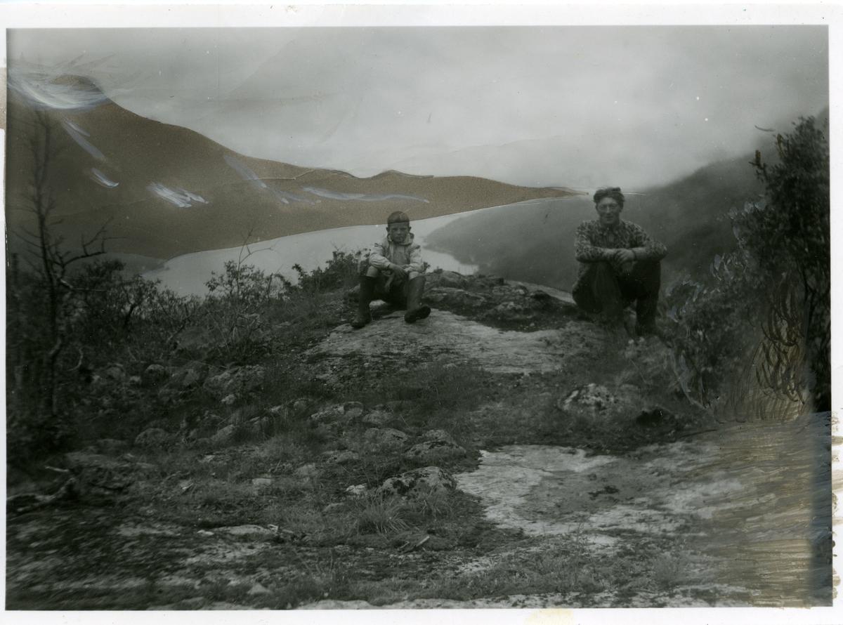 En gutt og en mann sitter foran utsikten over Vangsmjøsa.