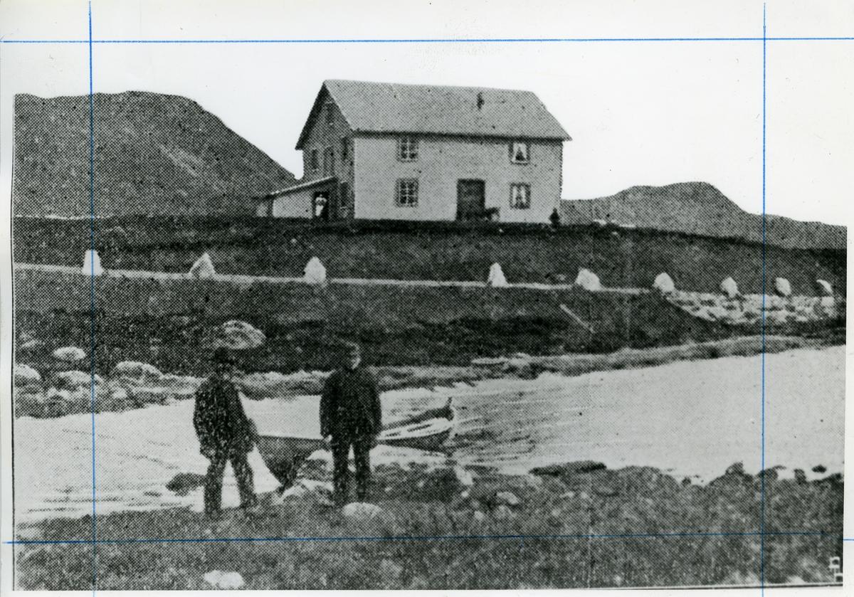 To menn står foran en båt ved en liten innsjø. I bakgrunnen er det et hus.