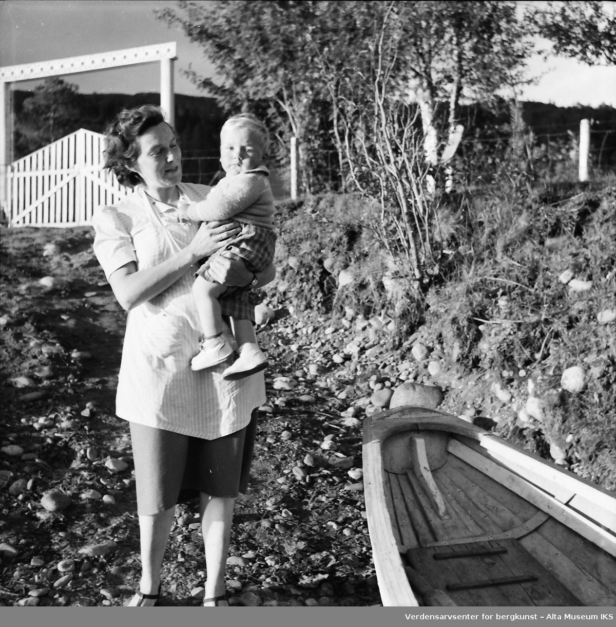 En kvinne holder et barn på armen på elvebredden.
