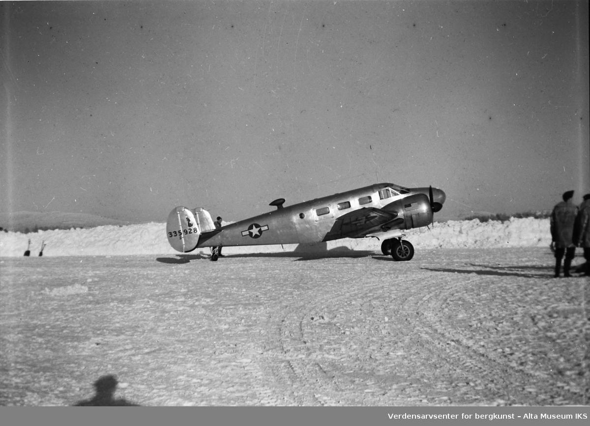 Amerikansk fly står parkert ved ved brøytekanten om vinteren. En mann står bak flyet, og en gruppe mennesker står til høyre i bildet.