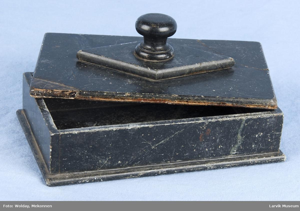 Form: a)rekt.framspr.bunn, glatte sider ...  b)flatt lokk,innsidig kant. dreiet knott på rombeformet midtparti.