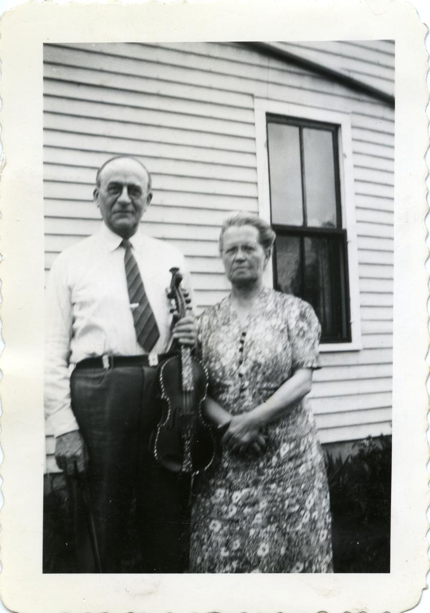 Portrett av et ektepar foran en husvegg. Mannen holder en hardingfele i hendene.