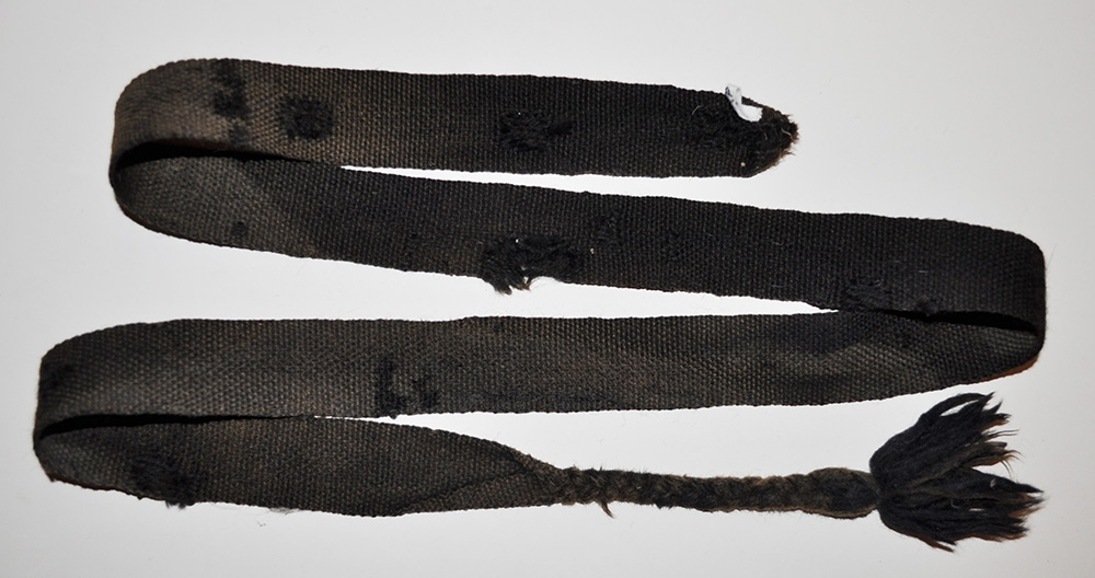 Benlinda i ull, bandvävd i tuskaft avslutas med fläta och tofs.