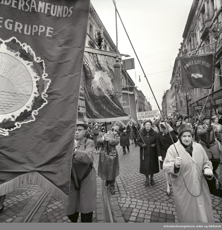 1. mai 1963 i Oslo.Demonstrasjonstoget i Karl Johans gate..Fane: Oslo Arbeidersamfunds Kvinnegruppe.Fane: Simensbråten og omegn kretslag og kvinnegruppe av DNA.Fane: Arbeiderpartiets Kvinnegruppe Vestkanten.Parole: Vi vil beholde Ekebergbanen!