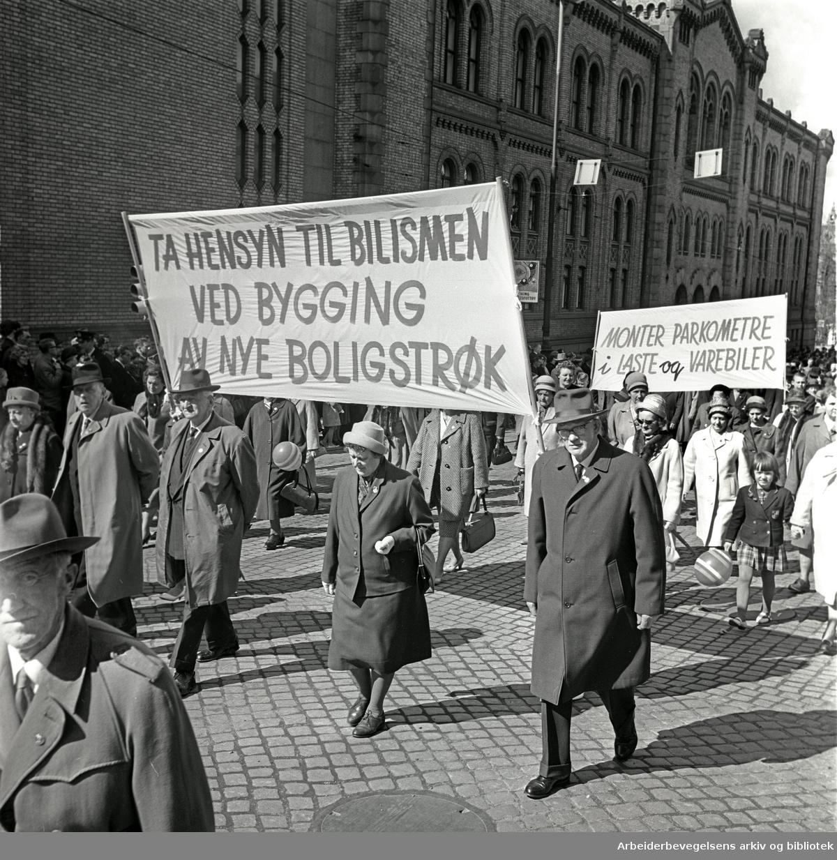 1. mai 1964 i Oslo.Demonstrasjonstoget i Karl Johans gate.Parole: Ta hensyn til bilismen ved bygging av nye boligstrøk.Parole: Monter parkometre i laste og varebiler