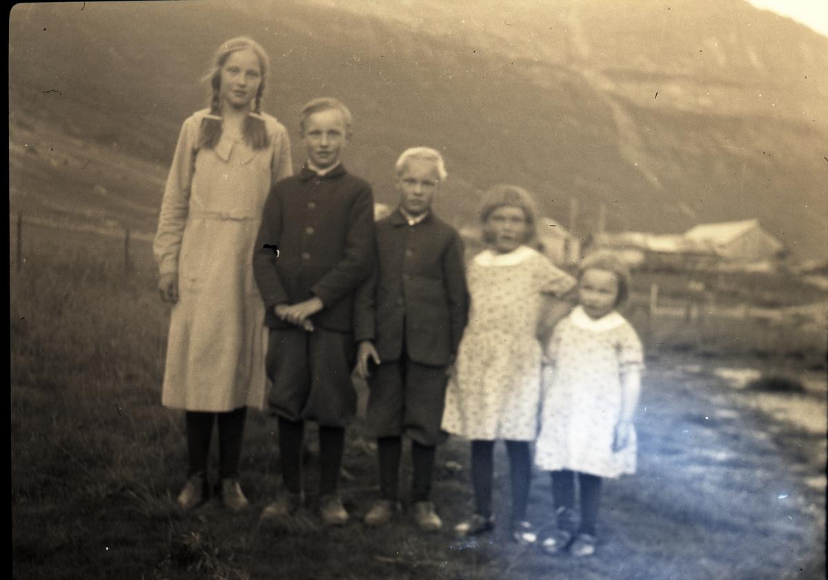 5 barn, 3 jenter og to gutter står ute, med flere gårdsbygninger i bakgrunnen. Guttene har mørke jakker og korte bukser og mørke strømper. Jentene har kjoler. Det opplyses at dette er barn fra Ellestad, Vestre Slidre.