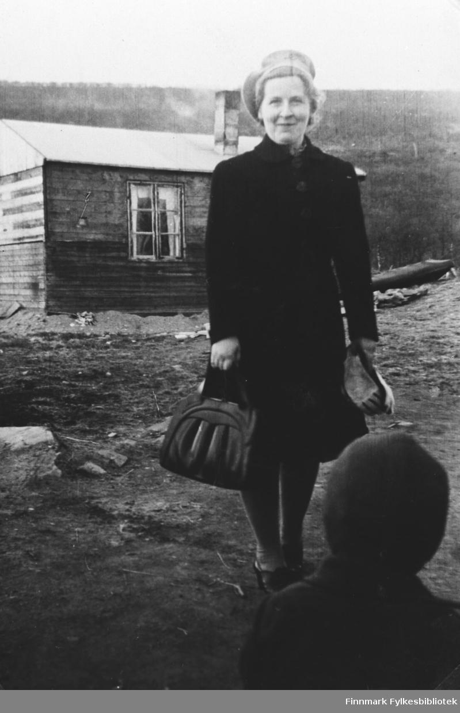 Lærer Gjerdrud Betten står foran en provosorisk bolig i Nesseby i gjenreisningstiden. Hun er kledd i en mørk kappe / jakke, basker og har en dameveske i handen. På forgrunnen foran henne står en liten gutt med ryggen til kamera.