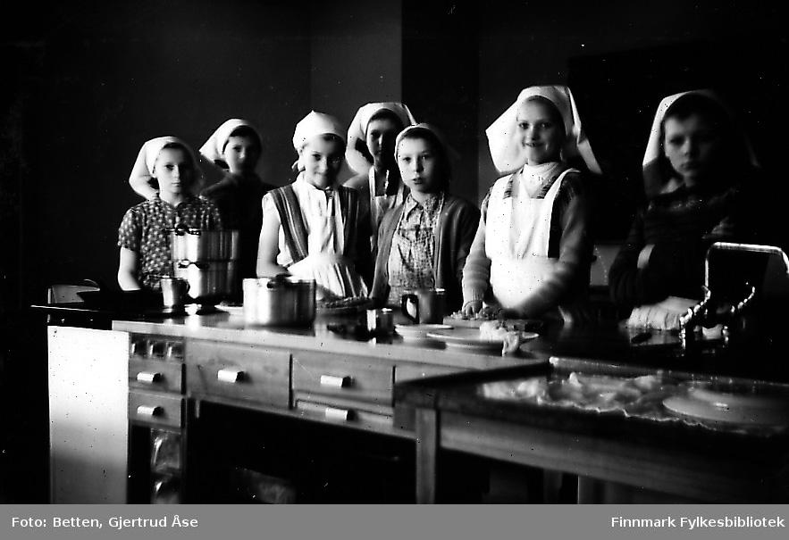 Jenter fra Smalfjord på kjøkkenopplæring i Seida skole og internat. Syv jenter kledd i forklær og tørkler står inne i skolekjøkkenet ved kjøkkenbenken. Jente nr 2 fra høyre heter Ragnfrid Johannessen (gift Mathisen).  Astri Dalsbø skal også være en av disse jentene.