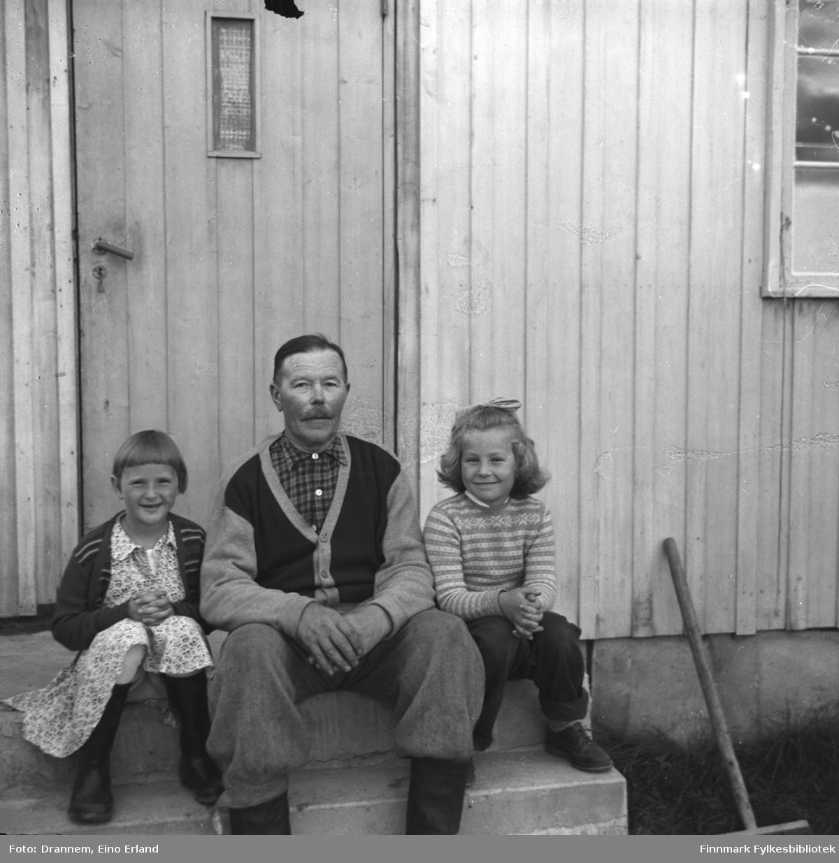Alfred Karikoski, Turid Lillian og en gjest (ei jente til venstre) sitter på trappen utenfor huset i Steinnes i Neiden