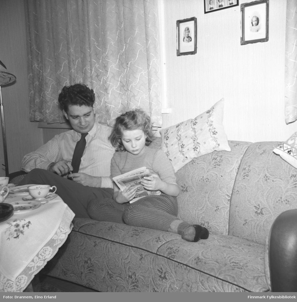 Turid Lillian og Asbjørn Gabrielsen på sofaen ved bordet som er klar for kaffe- og kakeservering. Turid Lillian leser intensivt tegneserien