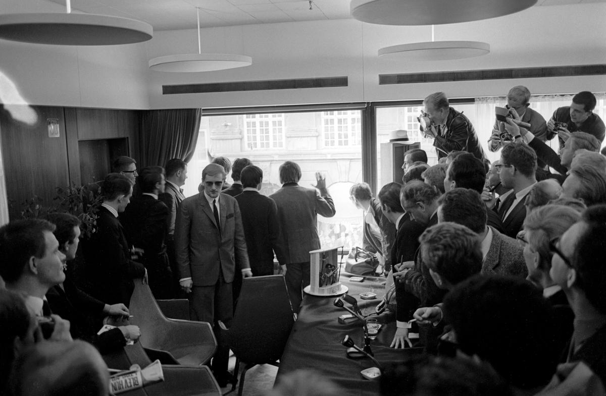 Det engelske bandet The Beatles skal ha konsert i København. Pressekonferanse med popgruppas medlemmer. Her vinker George Harrison, Paul McCartney, John Lennon og Jimmy Nicol til publikum utenfor hotellet.