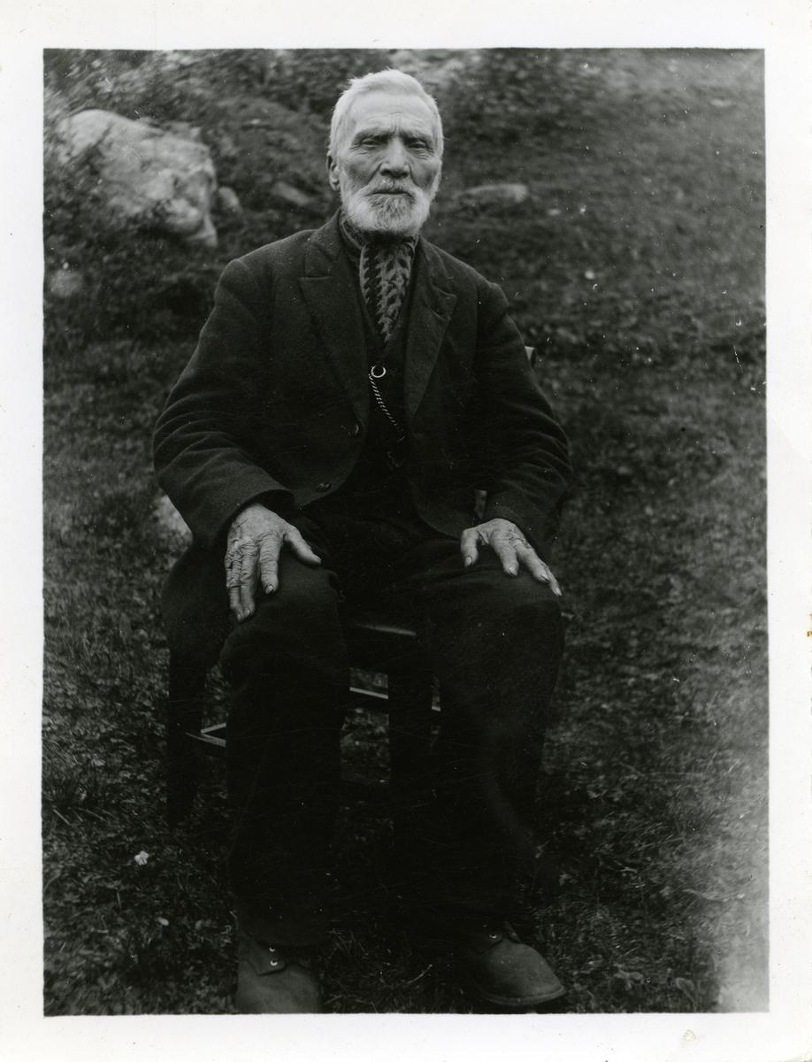 Portrett av mann sittende på en stol i en hage. Mannen er iført dress med skjerf i halsen.