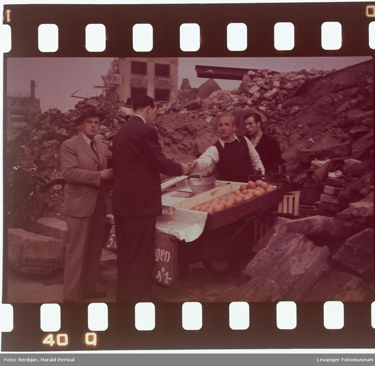Fra Tyskland i forbindelse med deltakingen på den årlige Fotomessen i Køln. Mann selger appelsiner i ruinene.