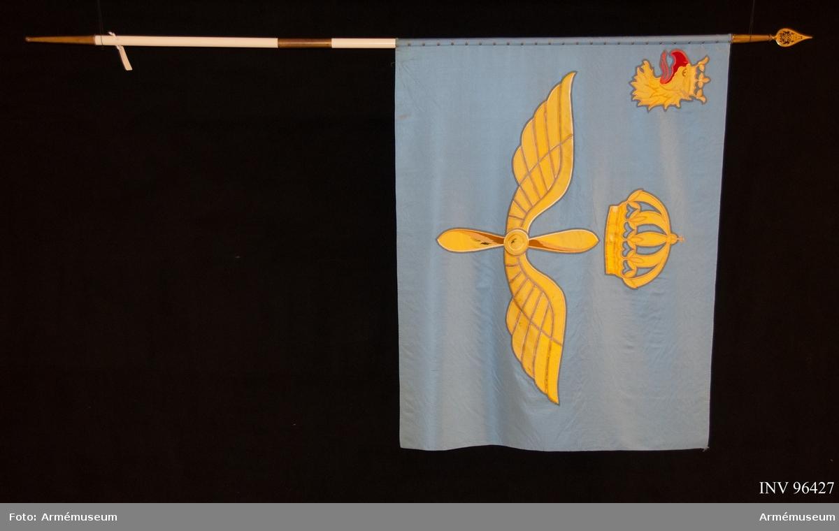 Duk av ljusblå kypertvävd siden. Fållad. Motivet utfört i intarsia och läggsöm i silketråd. Handbroderad. Föreställande en vingad, tvåbladig propeller under en kunglig krona, allt i gult. I övre inre hörnet landskapet Skånes vapenbild; ett avslitet gult griphuvud med tunga och beväring i rött. Motivet överfört på ny duk.  Delbar stång med doppsko. Spets med Gustav V:s monogram.  KT 2011-10-27