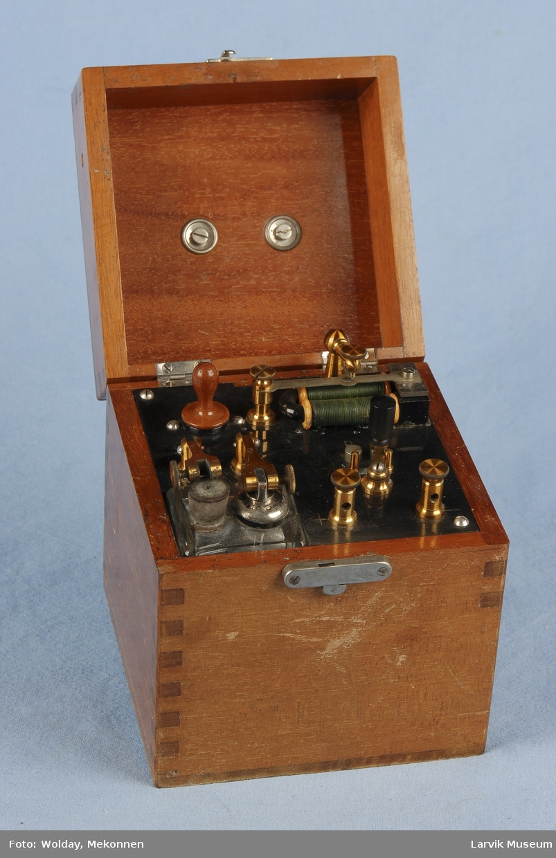 """Form: Kvadratisk boks med hank på lokket,  skuff på den ene siden med ekstrautstyr. To flate metall stenger. To sirkel metallplater som kan skrus på skaft. En metallbørste som kan skrus på skaft, En liten og en litt større stoff""""pute"""" til å feste på skaft.To metallsylindere, To skaft av tre og skru inntetning nederst i metall.Under lokket på boksen er det flere deler. Bl.a. en glassbeholder med to hull i toppen. En med lokk og en med kork. En svart sylinder med tre topp. Denne sylinderen er påklistret lapp med tall fra 0 - 10-"""