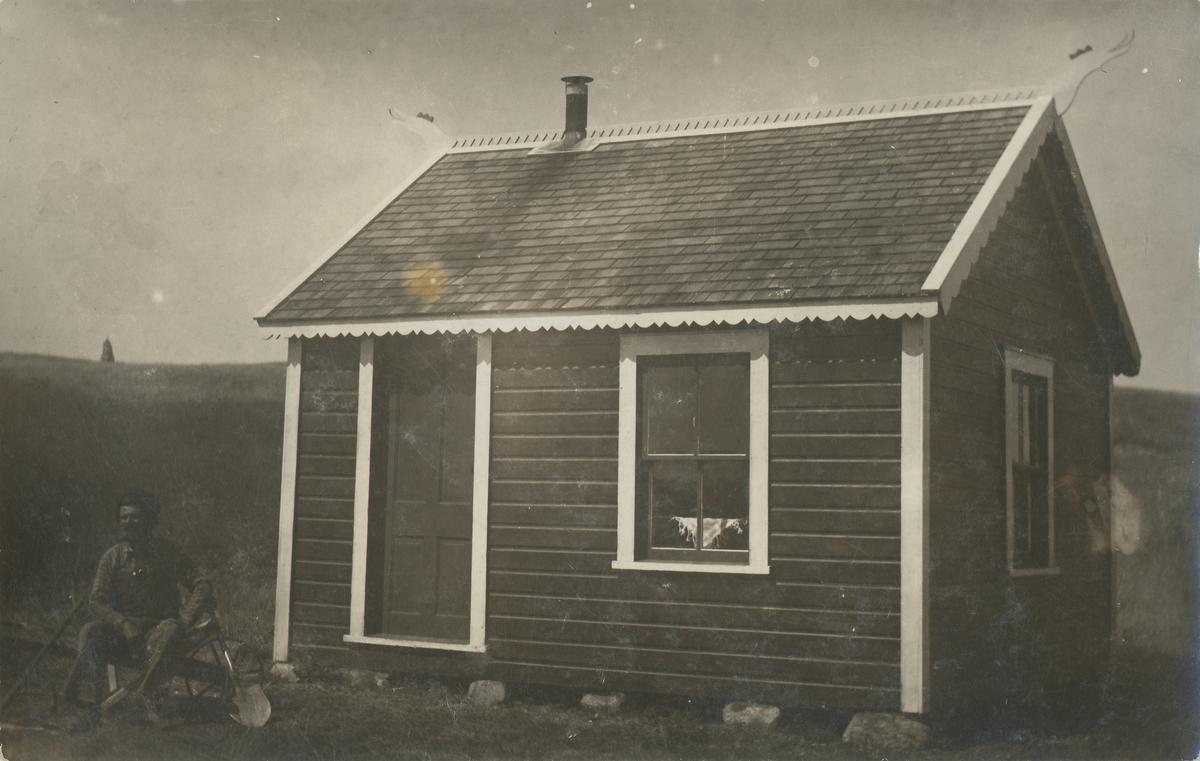 """En mann sitter ved et stovehus med dragehoder på endegavlene. Stova tilhørte Ingvald Skjeldrup og ble kallt """"Haukelid"""""""