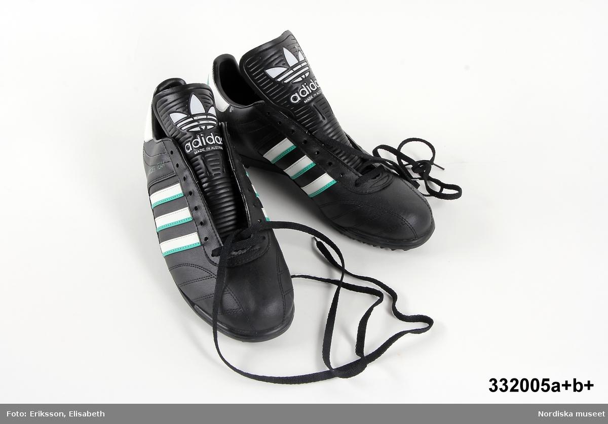 Ett par fotbollsskor. Skorna är svarta med vita och gröna ränder. Adidas logotyp finns på tre ställen på vardera sko. Text på utsidan av skorna: Soccer team. Sko av PVC-plast.  Svarta skosnören av syntet. Storlek 43 1/3. Anm: Oanvända. /Johanna Skoglund 2013-05-28