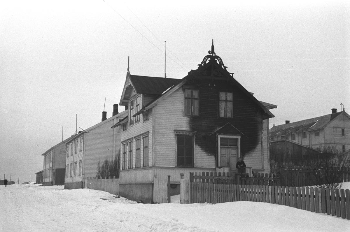 Et brannskadet hus i Vardø fotografert av arkitekt Ola Hanche-Olsen i påsken 1947 under en tur med Hurtigruta.   Ola Hanche-Olsen som har tatt bildene er født 13. mars 1920 i Borre, død 11. februar 1998 i Gjettum. Han var arkitekt og barnebokforfatter. Han hadde artium fra 1939, arkitekteksamen fra NTH 1946 og arbeidet deretter ved Finnmarkskontoret 1946–48 før han etablerte egen arkitektpraksis. Han debuterte som barnebokforfatter i 1974 med lettlestboka Knut og sjørøverne, og skrev i alt 12 bøker. Han var XU-agent 1944-45, og var også en aktiv fjellklatrer og friluftsmann. Ola var gift med Solveig Hanche-Olsen (f. Falkenberg); de fikk 3 barn, blant dem matematikeren Harald Hanche-Olsen. XU var den største og viktigste allierte etterretningsorganisasjonen i det okkuperte Norge under andre verdenskrig. Det meste av XUs virksomhet ble holdt hemmelig til 1988. Arkitektene Solveig og Ola Hanche-Olsen arbeidet ved Brente Steders Reguleringskontor i 1946. Hovedadministrasjon for gjenreisning av Nord-Troms og Finnmark ble lagt til Harstad og fikk navnet Finnmark kontoret. Landsdelen Nord-Troms og Finnmark blev oppdelt i syv distrikt med hver sin administrasjon. Honningsvåg, distrikt IV, skulle betjene Nordkapp, Lebesby, Porsanger og Karasjok kommune.