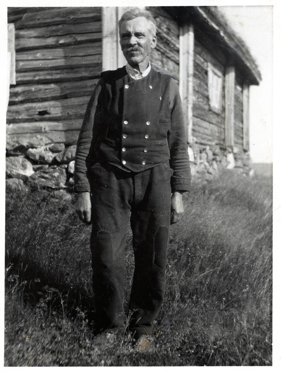 Portrett i helfigur av en mann foran en støl.
