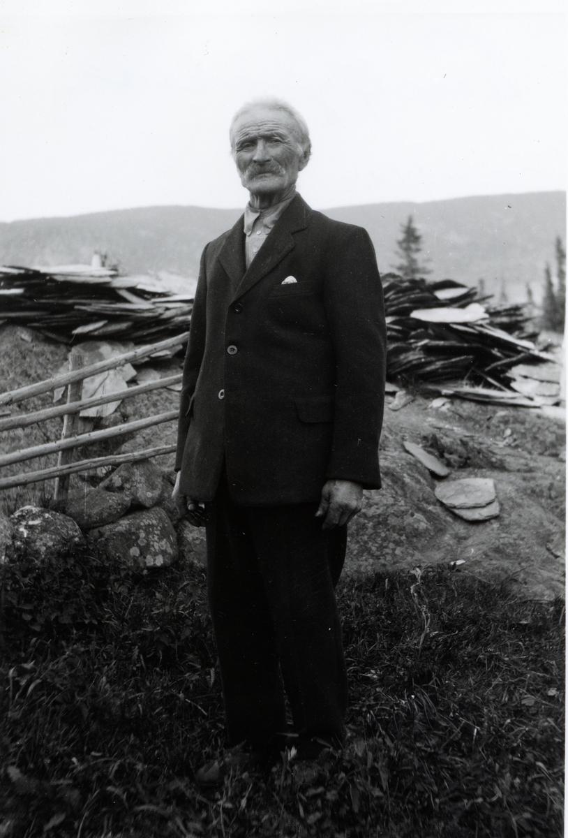 Portrett av mann i helfigur.Mannen er iført en mørk dress med lys skjorte. Mannen er avbildet foran et gjerde med en del skiferplater i bakgrunnen.
