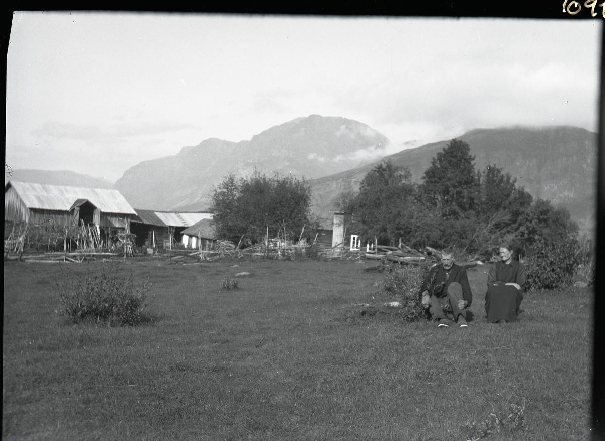 En mann og en kvinne sitter avbildet på en plen foran noen busker. Kvinnen er iført en kjole mens mannen er iført en mørk dress. I bakgrunnen vises gården.