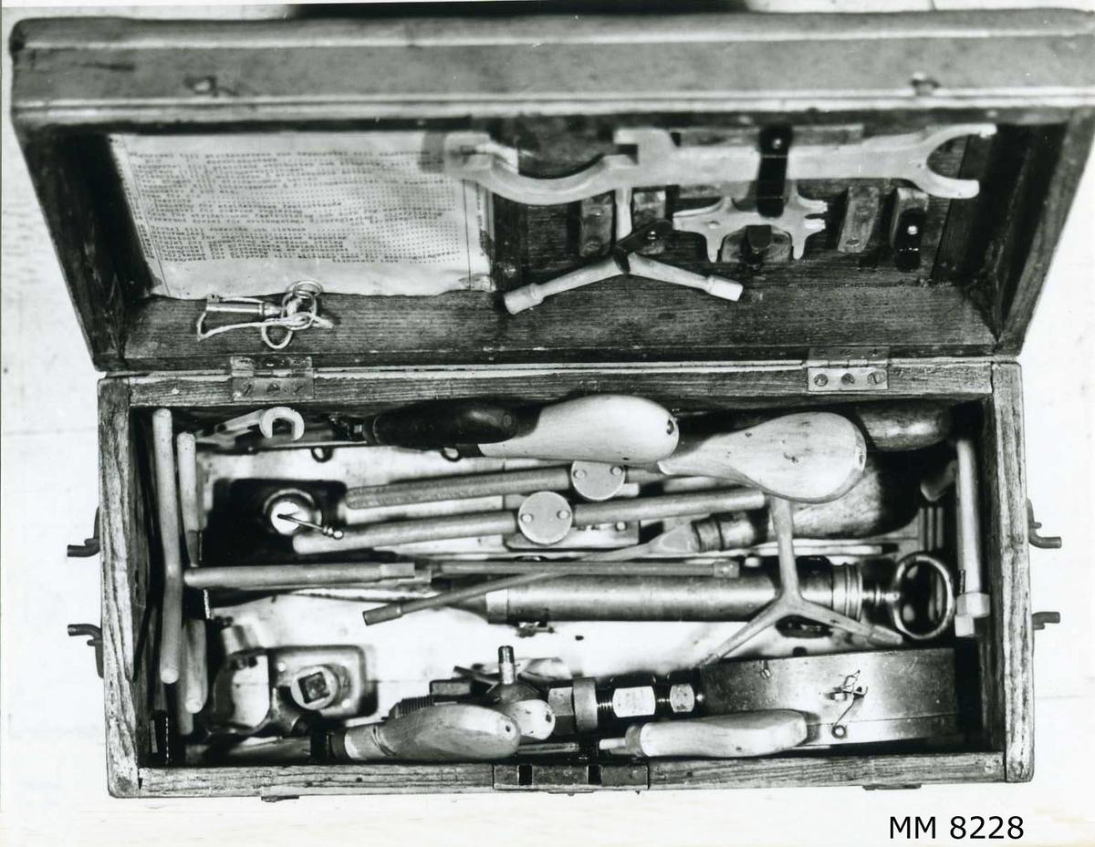 """Skjutlåda av trä för torpedverktyg. Innehåller diverse verktyg, såsom  skruvnycklar, toppnycklar, fettspruta, manometer m.m. På locket en metallbricka märkt: """"Skjutställ nr 9  45 cm m/02.  38 cm m/93 C,  35 cm m/03.  m/03 A.""""."""