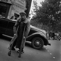 Paris. En handikappad man på kryckor tar sig över gatan.