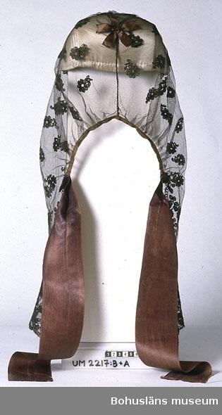 Sorgslöja av svart bomullstyll, blekt till mörkbrun färg. Broderat mönster (s.k. trädd spets eller tyllbroderi) med silke. Mönstret består av en 13 cm bred bård med ett stiliserat blommönster längs nederkanten och ovanför kanten spridda blommor över hela ytan. Längs nederkanten och sidorna bak är kanten klippt i runda uddar som följer broderimönstret. Upptill är slöjan sammansydd, med en ca 15 cm lång söm bak, och ihop- rynkad så tyget får rundad form fram. Mitt över hoprynkningen sitter en dekoration, en bandrosett av smalt sidenband. Bak är två, 7 cm breda ca 50 cm långa, sidenband fastsydda, ett på varje sida. De sitter ca 32 cm upp från nederkanten räknat, där uddkanten längs sidorna bak tar slut. Den resterande kanten bak är tyget rynkat och kantat med ett smalt sidenband. Sidenbandet längs kanten bak är mycket sliten. En reva och småhål i tyllen mitt fram, ytterligare små hål bak och på några ställen på vänster sida. Dateringen gjord efter samtal med Ann Resare, Skansens klädkammare, som berättade att sorgflor kom i det borgerliga dräktskicket på 1890-talet. Mössan som bars under floret kan dock vara gjord tidigare. Hängdes över huvudet med bindmössa UM002217:A under. Knöts bak.  Ur handskrivna katalogen 1957-1958: Sorgdok. Sorgdok, svart tyll m. broderade svarta blommor, två fastsydda svarta sidenband. Helt.