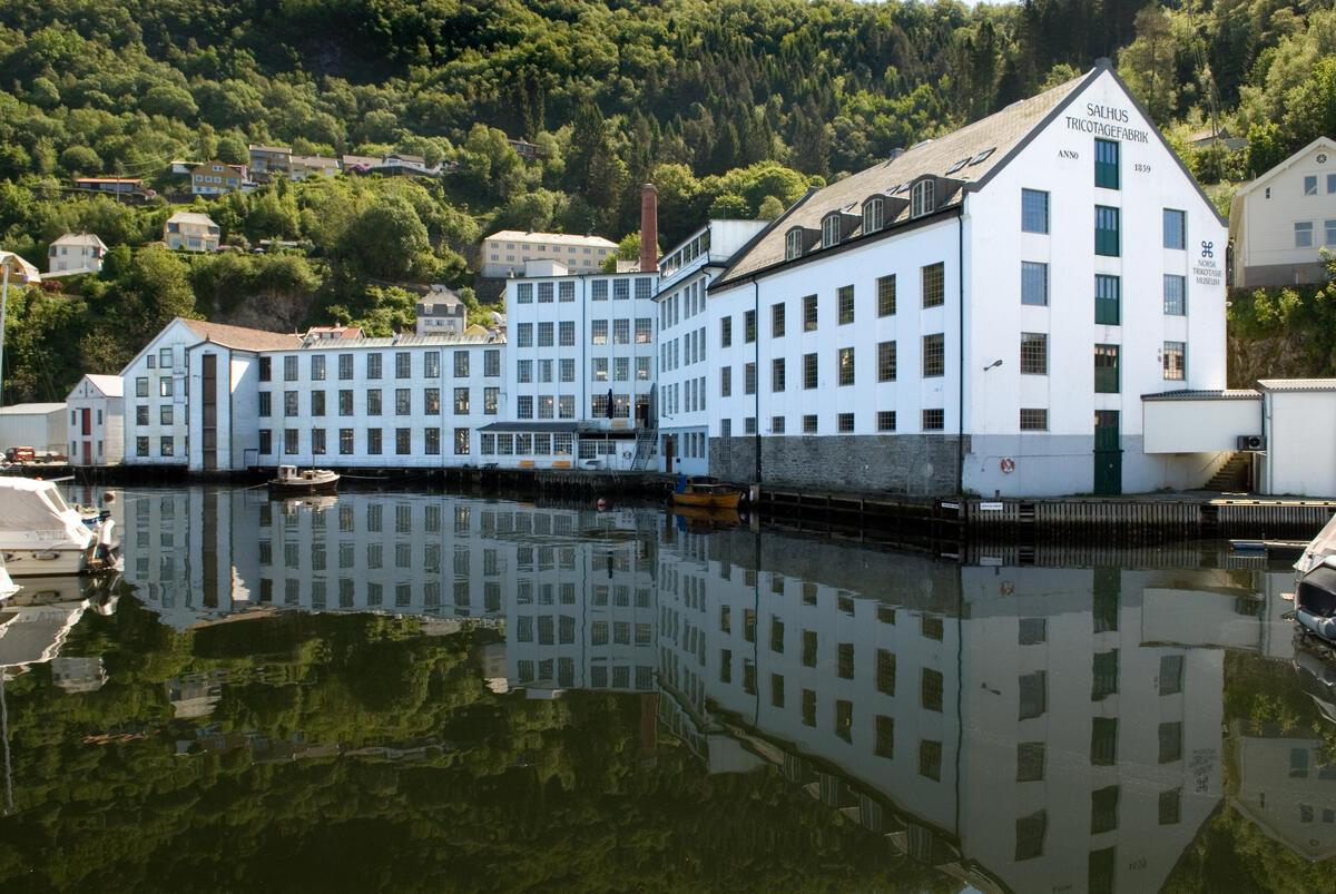 Bygda Salhus utanfor Bergen, med den tidlegare tekstilfabrikken Salhus Tricotagefabrik sett frå sjøen. (Foto/Photo)