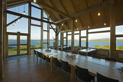 Interiør med langbord, vindauge med utsikt over kystlandskap. Foto. Foto/Photo