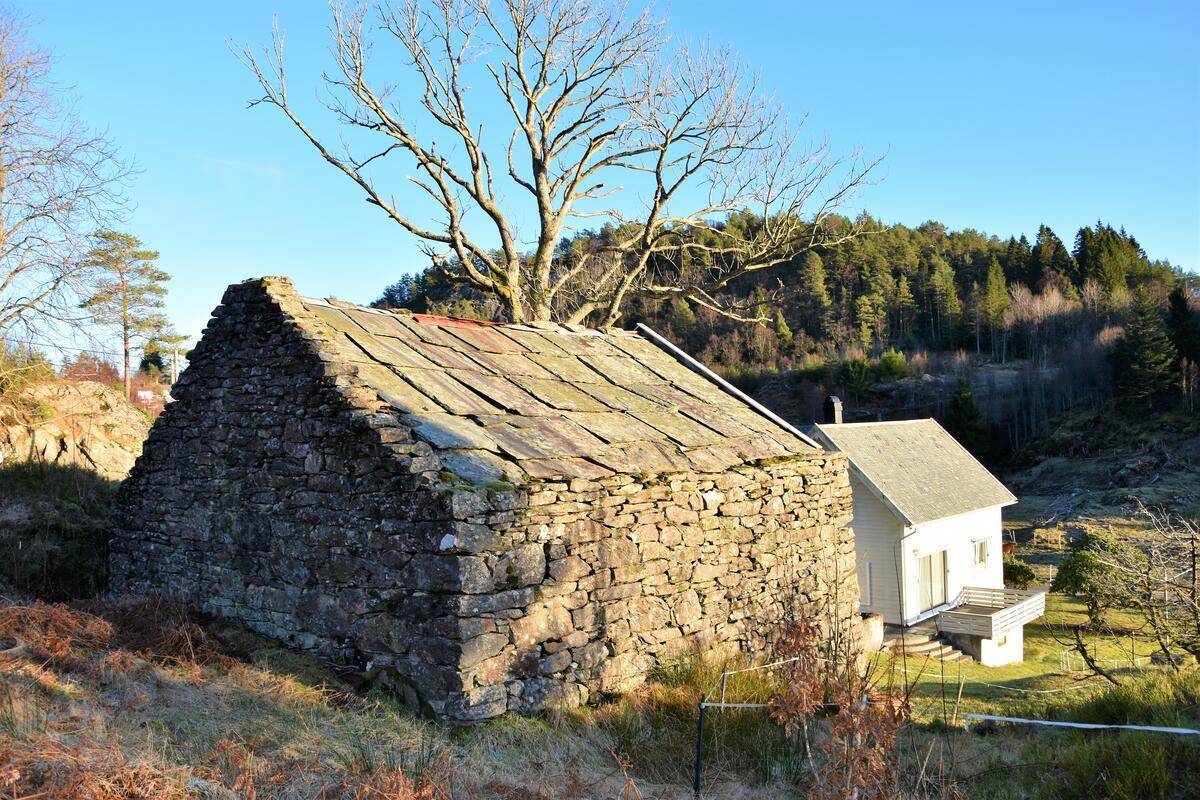 steinløe med eit tre og eit kvitt trehus bak, solskin på landleg landskap (Foto/Photo)