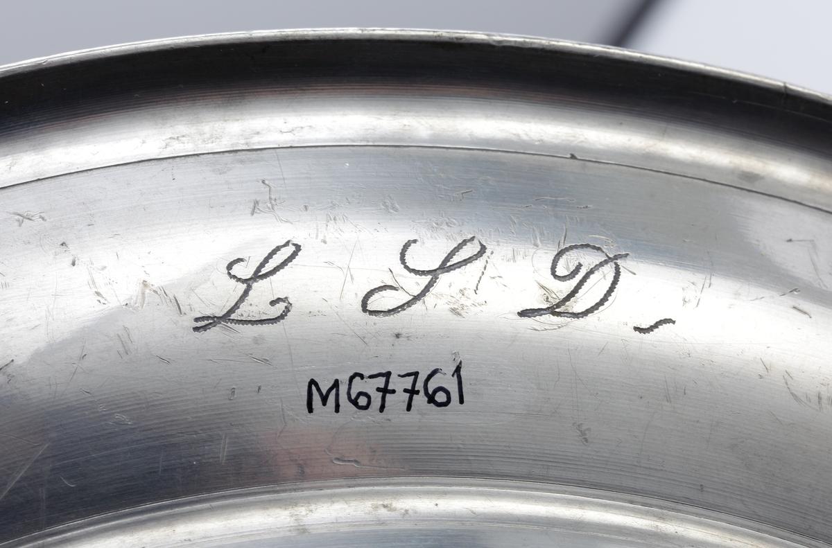 """Ett st. djupt, runt fat av tenn.  Stämpel (tre kronor) i fatets spegel. Ägarinitialer på brämens undersida: """"L.S,D.""""  Stämplar i botten."""