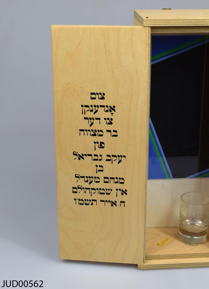 Låda tillverkad av trä för havdala. Enkel och rak utformning. Öppning framtill med dubbla dörrar dekorerade med varsin davidsstjärna målad i svart. Inuti lådan finns tre små glas, kryddor och havdalaljus. Fonden är dekorerat med abstrakt geometrisk konst signerad Peter Freudenthal. På vänstra dörren dedikationstext på jiddisch, på högra dörren välsignelser för havdalaceremonin på hebreiska. Numrerad 37/77.