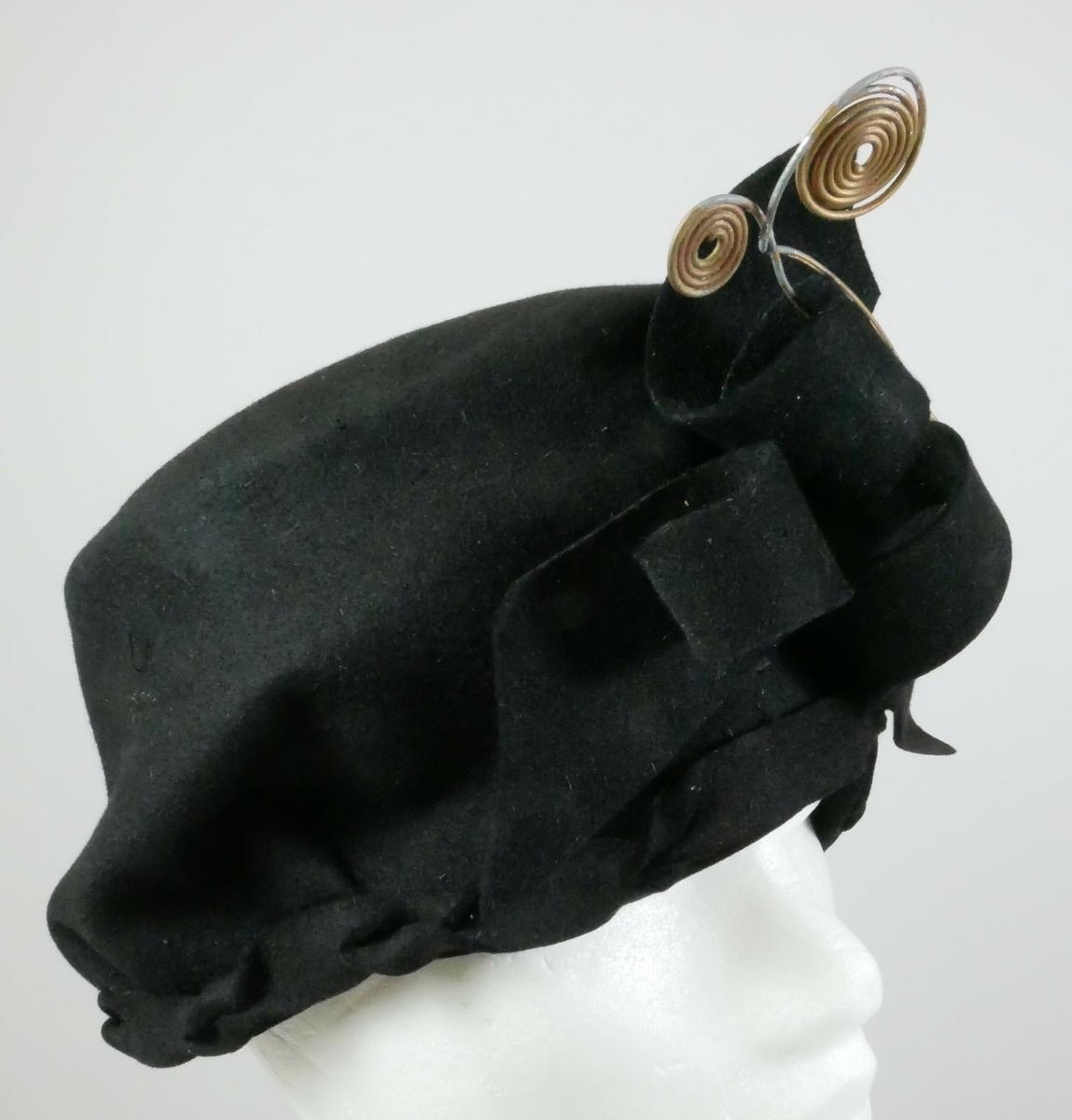 Svart hatt med dekorelementer foran i svart tekstil og metall.