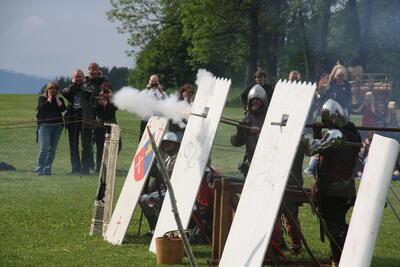Menn kledd i middelalderrustninger gjemmer seg bak trepalisader med hull til løpet på håndholdte kanoner. Den ene kanonen har akkurat avfyrt, så røyken tyter ut av åpningen i palisaden.. Foto/Photo