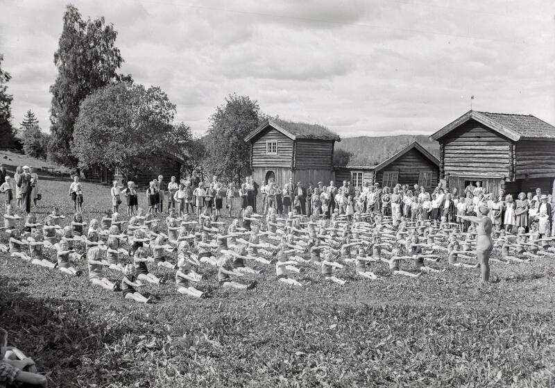 Barn sitter i rekker og øver på svømmetak etter instruksjon fra svømmelæreren. Rundt står foreldrene og ser på. Museumsbygninger i bakgrunnen. (Foto/Photo)