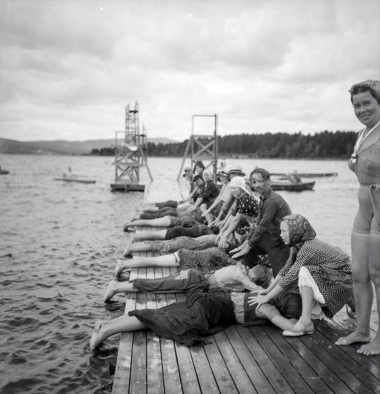 Barn ligger påkledd på magen på en brygge mens de har hver sin medhjelper til å trene på svømmeteknikk. (Foto/Photo)
