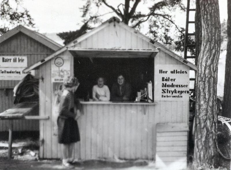 Kioskbod med to personer i luka og en kunde utenfor. Plakat til høyre for luka annonserer med utleie av båter, madrasser, strykejern og barbermaskiner. (Foto/Photo)