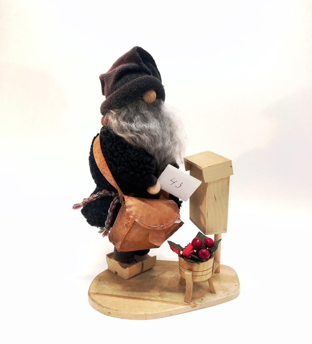 Figurin förställande en tomte med postväska och ett brev i handen. Tomten står vid en postlåda.