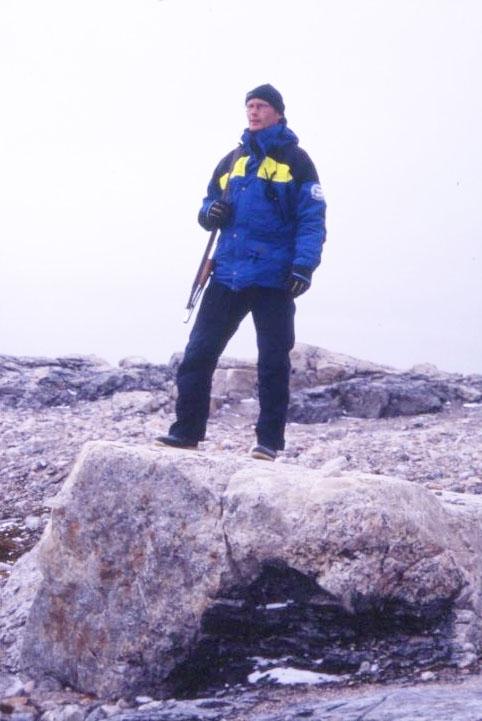 En man i Polarforskningssekretariatets kläder med gevär över axeln står på en större sten. Han är björnvakt i samband med utgrävning av Andréelägret på Vitön.