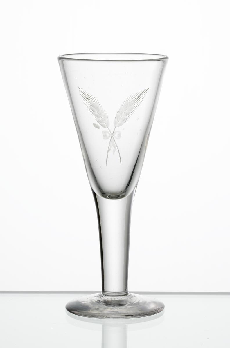Design: Edward Hald. Brännvinsglas, konisk kupa med graverat motiv i form av två korslagda sädesax sammanbundna med en rosett, på kupan.
