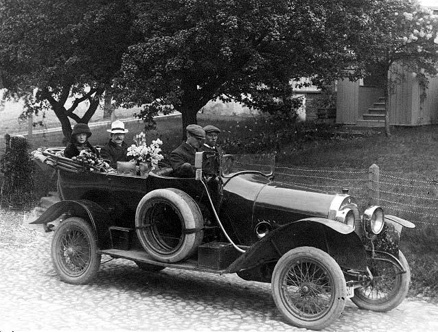 En bil (cabriolet) står på Brahegatan i Gränna, vid torgets södra uppfart, riktning söderut. I bilen sitter två män fram samt en kvinna och en man i baksätet, med blommor. Mannen bakom ratten är troligen doktor Eurén från Jönköping.