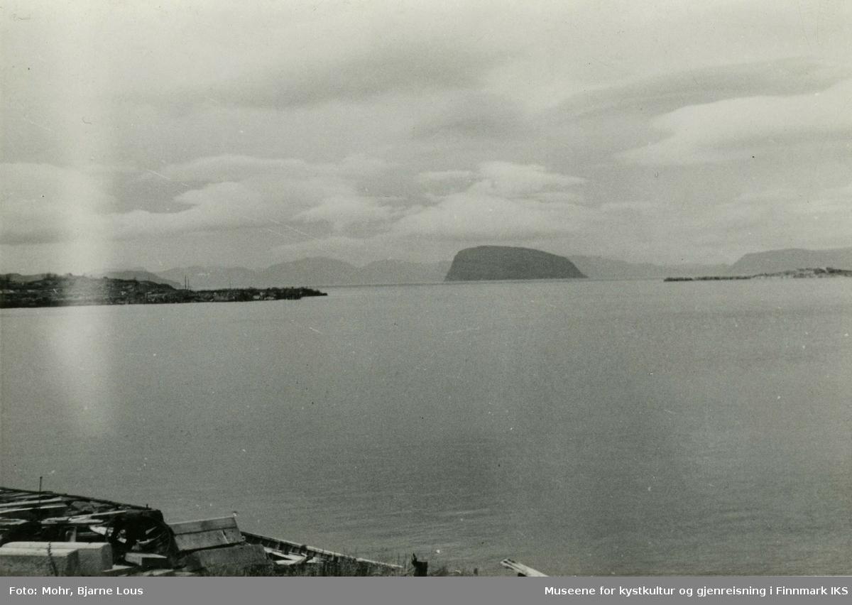 Utsikt fra det ødelagte Hammerfest ut til Sørøysundet og Håjafjellet. Til venstre ser man ruinene av bykjernen og til høyre Fuglenesodden. Himmelen er overskyet.