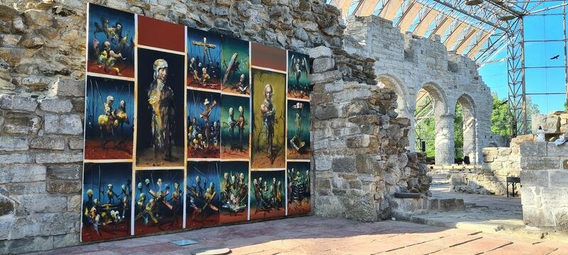 Fargerikt oljemalericollage i flott kontrast mot den lyse kalksteinen, og kirkeruinbuene i bakgrunnen. (Foto/Photo)