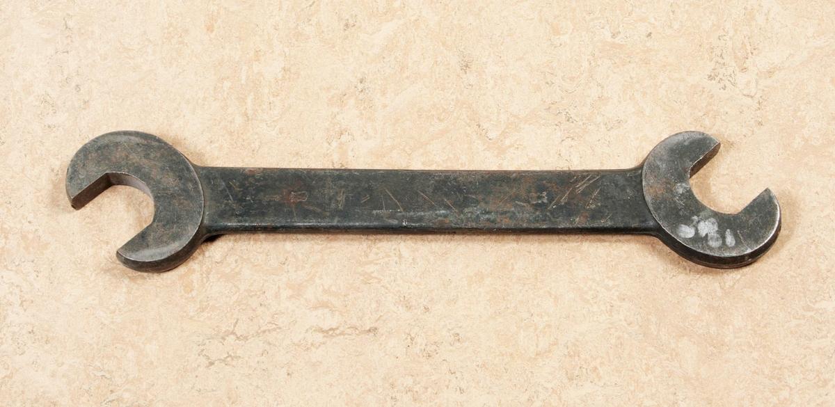 Fast nyckel av stål. Kallad dubbel U-nyckel. Proveniens Fritz Sjöbloms Trikåfabrik, Borås.