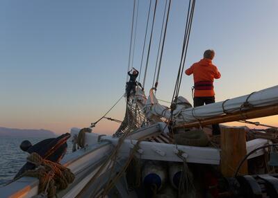 Men står utkikk forut i en seilbåt i soloppgang.. Foto/Photo