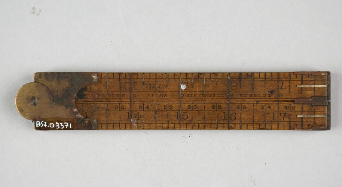 Lengdemål. Tommestokk, sammenleggbar av tre, med hengsler og beslag av messing. I fire deler som kan foldes sammen/brettes ut.