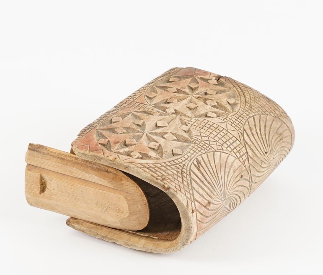 Ei bokforma øskje. Sjølve øskja er skore ut i eitt stykkje tre. Øskja har hatt to lok, eit i kvar ende, men har no berre eitt. Øskja er rikt dekorert med karveskurd.