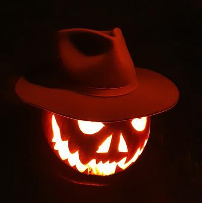 Lysende gresskar med cowboyhatt i mørket. Foto/Photo